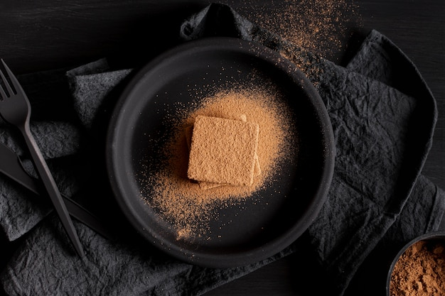 ブラックプレートとナプキンにミニマルなチョコレートパウダー