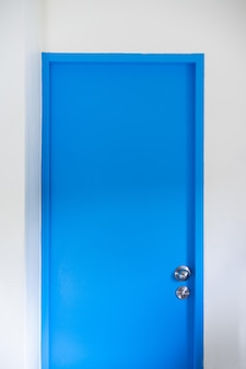 Minimalist clean blue door with grey wall. minimalist interior .