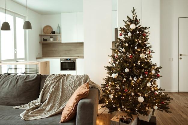 미니멀리스트 선물, 소파, 격자 무늬가있는 크리스마스 트리로 장식 된 편안하고 아늑한 거실. 크리스마스 축하 장식.