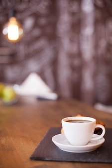 Minimalist composition of a cup of coffee on a black stone plate with blurred background. tasty coffee. vintage pub.