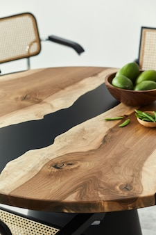 Minimalist composition on the design wooden table with fruits, nuts and stylish chair. modern dining room.