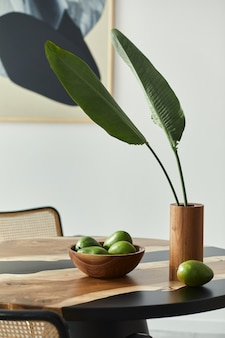 Minimalist composition on the design wooden table with fruits, tropical leaf in vase, abstract painitngs and stylish chair. modern dining room.