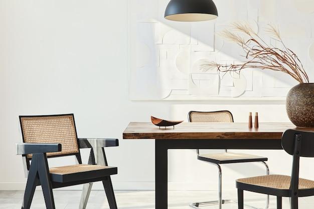 Минималистичная композиция интерьера столовой с деревянным столом, дизайнерскими стульями, засушенными цветами в вазе, черным подвесным светильником, художественной росписью на стене и элегантными личными аксессуарами.
