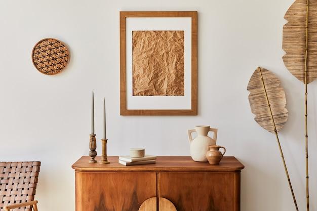 Минималистичная композиция гостиной с коричневой рамкой для картин, растением, ретро-креслом, засушенным тропическим листом, украшениями и элегантными личными аксессуарами в стильном домашнем декоре.