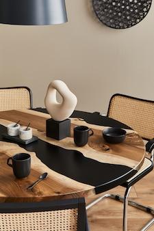 黒のティーポット、カップ、スプーンを備えたデザインの木製とエポキシのテーブルのミニマリストの構成。モダンなダイニングルームのインテリア。詳細。テンプレート... Premium写真