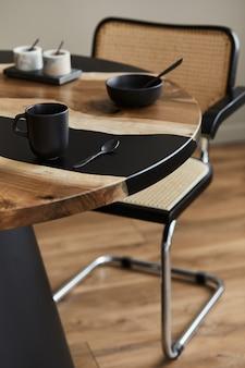 黒のティーポット、カップ、スプーンを備えたデザインの木製とエポキシのテーブルのミニマリストの構成。モダンなダイニングルームのインテリア。詳細。テンプレート...