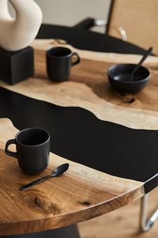 Минималистичная композиция на дизайнерском деревянном и эпоксидном столе с черным чайником, чашками и ложкой. интерьер современной столовой. подробности.