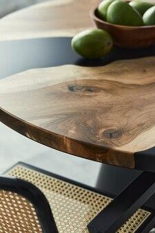 フルーツ、ナッツ、スタイリッシュな椅子を備えたデザインの木製テーブルのミニマルな構成。モダンなダイニングルーム。