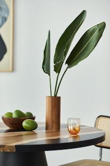 フルーツ、花瓶のトロピカルリーフ、抽象的な痛み、スタイリッシュな椅子を備えたデザインの木製テーブルのミニマルな構成。モダンなダイニングルーム。