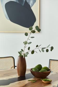 フルーツ、花瓶のトロピカルリーフ、抽象的な痛みとスタイリッシュな椅子を備えたデザインの木製テーブルのミニマリストの構成