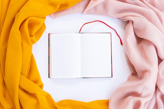Минималистическая концепция. книга на фоне коричневый шарф и желтый шарф на белом фоне. осень, осенняя концепция. плоская планировка, вид сверху, копия пространства