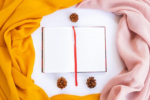 ミニマリストのコンセプト。背景の本白い背景に茶色のスカーフと黄色のスカーフ。秋、秋のコンセプト。フラットレイ、上面図、コピースペース