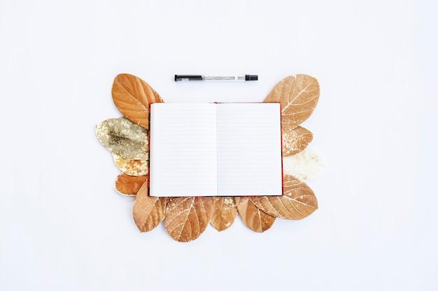 Минималистическая концепция. сухие листья, книга и ручка на белом фоне. осень, осенняя концепция. плоская планировка, вид сверху, копия пространства