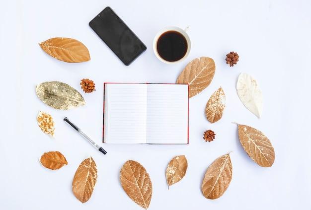 Минималистическая концепция. сухие листья, книга и ручка, цветок сосны, мобильный телефон на белом фоне. осень, осенняя концепция. плоская планировка, вид сверху, копия пространства