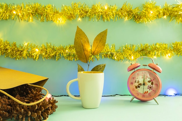 Minimalist concept idea displaying products. coffee mug on christmas and new year background. alarm clock. pine flower
