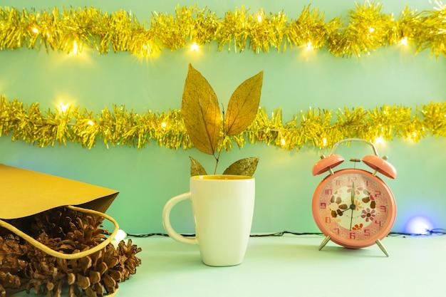 製品を表示するミニマリストのコンセプトアイデア。クリスマスと新年の背景にコーヒーマグ。目覚まし時計。松の花
