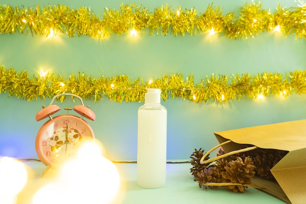 Minimalist concept idea displaying products. cosmetic bottles on christmas and new year background. alarm clock. pine flower