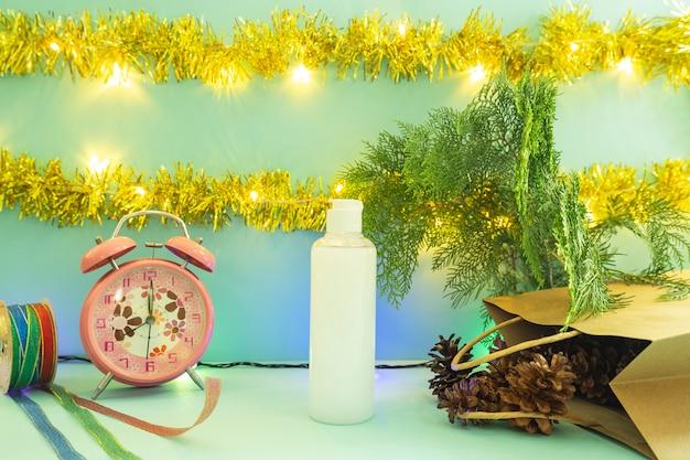 製品を表示するミニマリストのコンセプトアイデア。クリスマスと新年の背景に化粧品のボトル。目覚まし時計。松の花
