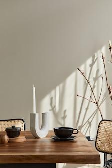 Минималистичная концепция интерьера столовой с деревянным семейным столом, дизайнерскими стульями, подсвечником, чашкой кофе, посудой, бежевой стеной и личными аксессуарами. скопируйте пространство. шаблон.