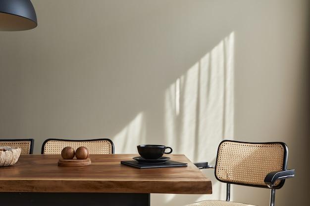 나무 패밀리 테이블, 디자인 의자, 커피 한잔, 식기, 베이지 색 벽 및 개인 액세서리가있는 식당 인테리어의 미니멀리스트 개념. 공간을 복사하십시오.
