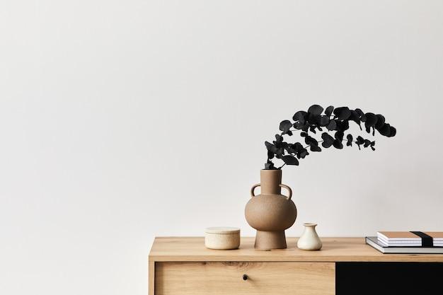 나무 옷장, 세라믹 꽃병의 잎 및 현대 가정 장식의 우아한 개인 액세서리가있는 우아한 아파트의 거실 인테리어의 미니멀리스트 개념. 공간을 복사하십시오. 주형. .