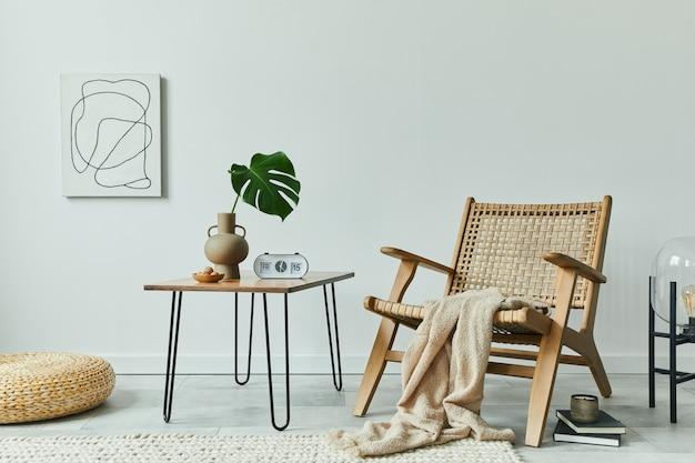 등나무 안락 의자 호두 커피 테이블 꽃병 시계 painintg 책 및 세련된 가정 장식의 개인 액세서리에 열대 잎과 거실 인테리어의 미니멀 개념