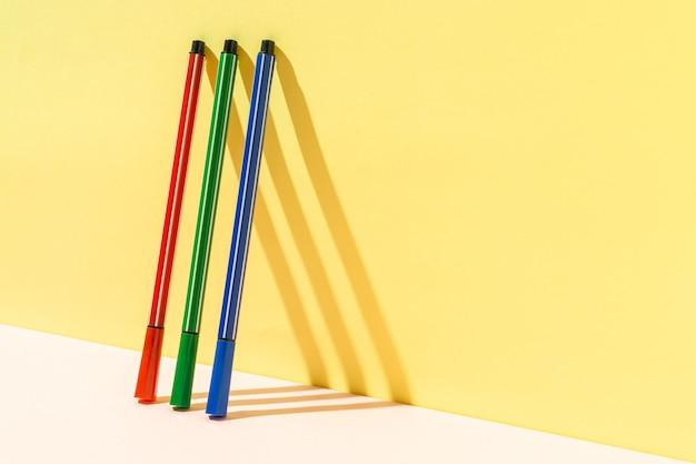 黄色の壁に赤、緑、青のペンのミニマリストの概念。