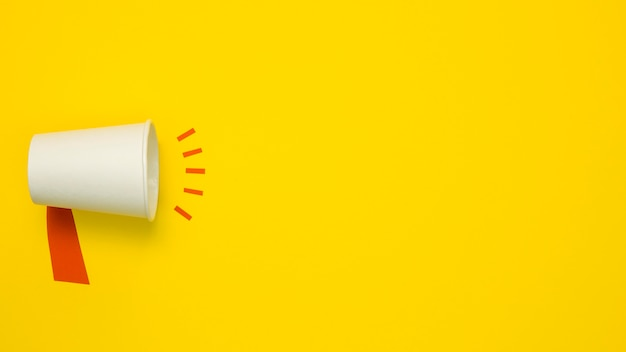 Concetto minimalista con megafono su sfondo giallo