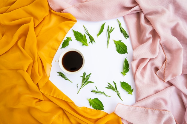 미니멀한 컨셉입니다. 흰색 바탕에 노란색 스카프, 갈색 스카프, 커피, 녹색 잎. 떨어지다. 평평한 평지, 평면도, 복사 공간
