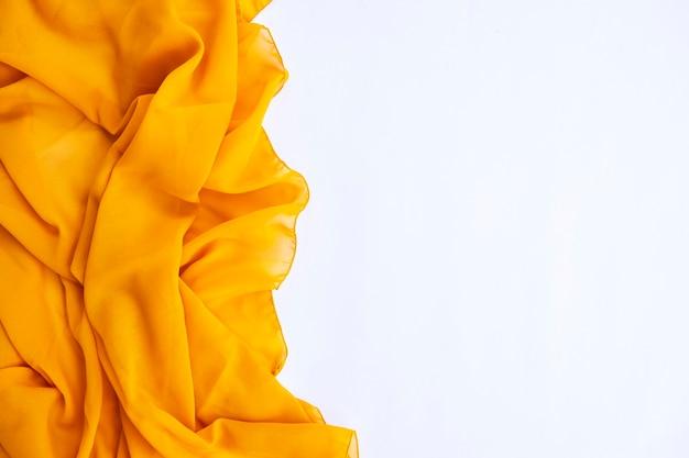 Минималистическая концепция. желтый шарф на белом фоне. осень, осенняя концепция. плоская планировка, вид сверху, копия пространства