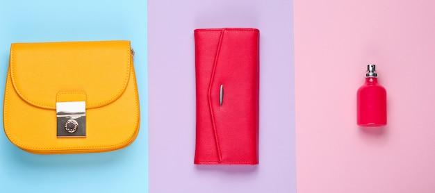 シンプルなファッション。レディースファッションアクセサリー。革製の財布、黄色のバッグ、香水瓶。上面図
