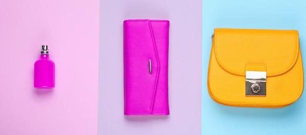 ミニマリストファッション。パステルカラーの背景に女性のファッションアクセサリー。革製の財布、黄色いバッグ、香水瓶。上面図