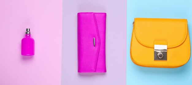 Minimalist fashion. women's fashion accessories on a pastel background. leather purse, yellow bag, perfume bottle. top view