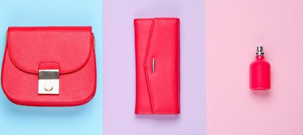 シンプルなファッション。女性の赤いファッションアクセサリー。革製の財布、バッグ、香水瓶。上面図
