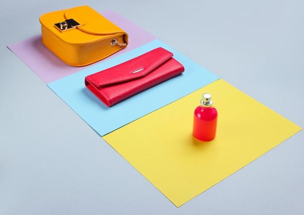 Минималистская мода. модные женские аксессуары. кожаный кошелек, желтая сумка, флакончик для духов. вид сбоку