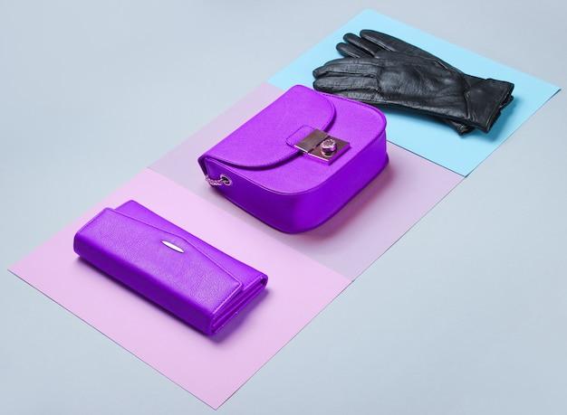ミニマリストファッション。パステルカラーの背景に女性の流行のアクセサリー。革製の財布、バッグ、手袋。側面図