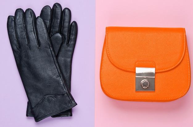ミニマリストファッション。パステルカラーの背景に女性の流行のアクセサリー。革製の財布、手袋。上面図