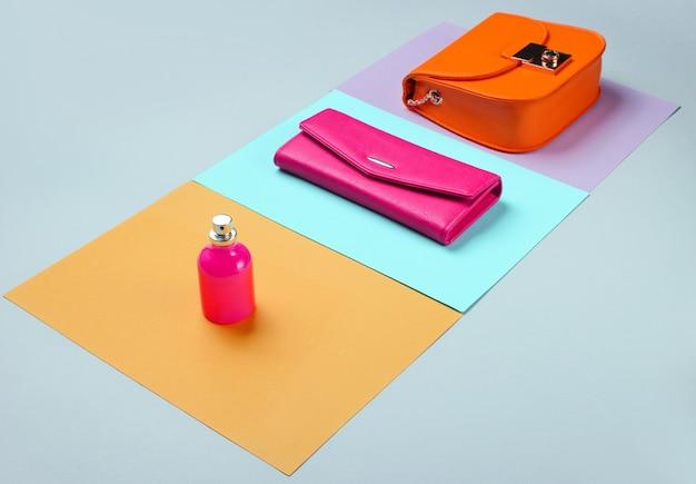 ミニマリストファッション。パステルカラーの背景に女性の流行のアクセサリー。革製の財布、黄色いバッグ、香水瓶。側面図