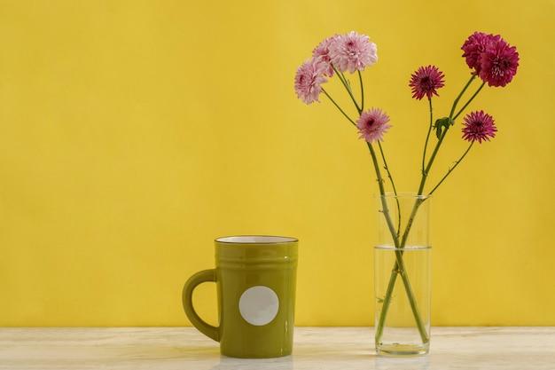 노란색 배경이 있는 대리석 테이블에 커피 한 잔 옆에 미니멀한 꽃꽂이