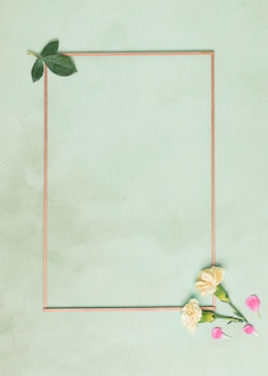 Minimalist frame with carnation flowers and leaves on blue background