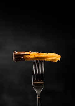 Minimalist fried churros in a fork front view