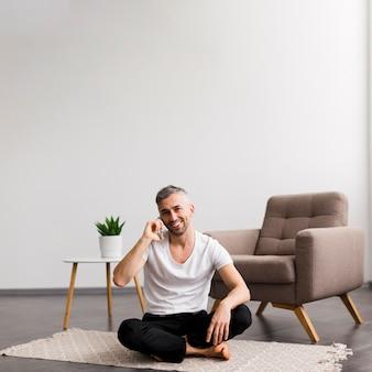 シンプルな家の装飾と床に座っている男