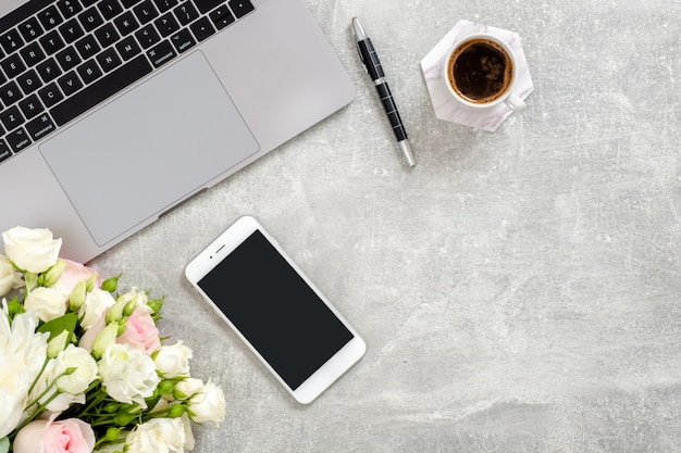 Minimalist home office desk with blank copy space mockup screen smartphone, laptop computer, coffee cup, flowers on concrete stone.
