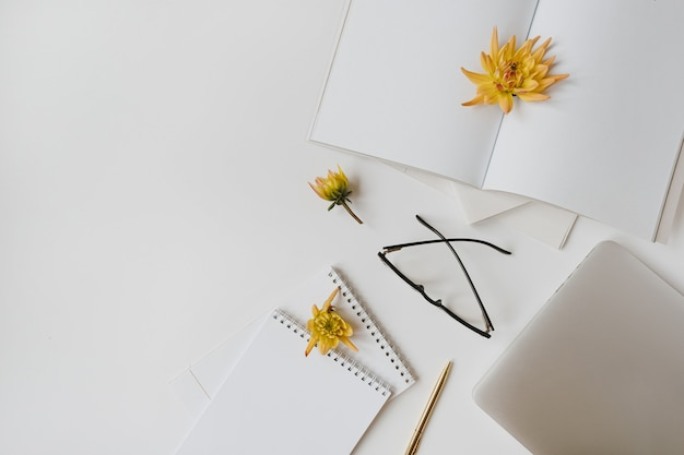 ミニマリストのホームオフィスデスクワークスペース。白紙のノート、ラップトップ、メガネ、黄色い花のつぼみ、文房具。フラットレイ、上面図