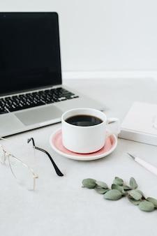 Минималистский рабочий стол домашнего офиса. ноутбук, кофе, очки, блокнот, эвкалипт