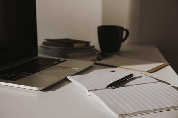 ミニマリストのホームオフィスデスクワークスペース。コーヒーカップ、紙のシート、白い壁に文房具とテーブルの上のラップトップ