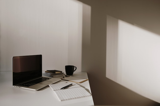 Minimalist home office desk workspace. laptop on table with coffee cup, paper sheet, stationery against white wall