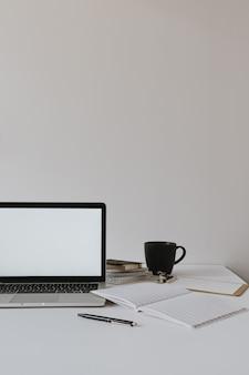 ミニマリストのホームオフィスデスクワークスペース。コーヒーカップ、紙のシート、白い壁に文房具とテーブルの上の空白のコピースペースを持つラップトップ