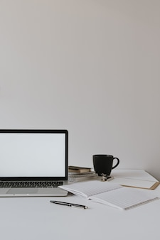 Minimalist home office desk workspace. laptop with blank copy space on table with coffee cup, paper sheet, stationery against white wall