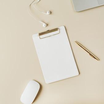 ベージュのクリップボード、ラップトップ、ヘッドフォンを備えたミニマリストのホームオフィスデスクワークスペース